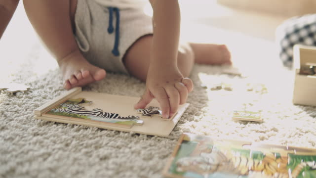 asian baby play jigsaw on the floor. - puzzle stock videos & royalty-free footage