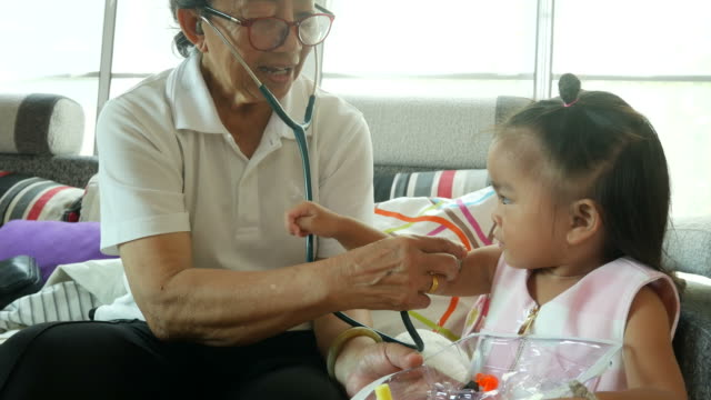 Asian baby playing doctor and patient  with grandmother