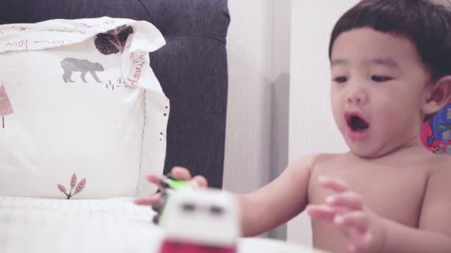 asiatiska baby spelar toy på sängen - endast en pojkbaby bildbanksvideor och videomaterial från bakom kulisserna