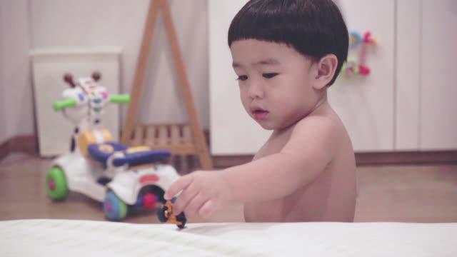 stockvideo's en b-roll-footage met aziatische baby speelgoed spelen op het bed - alleen één jongensbaby