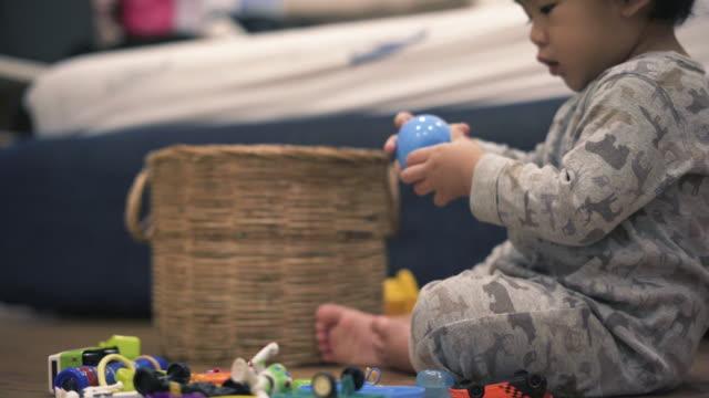 vídeos de stock, filmes e b-roll de bebê asiático que jogam o brinquedo no chão - sala de estar
