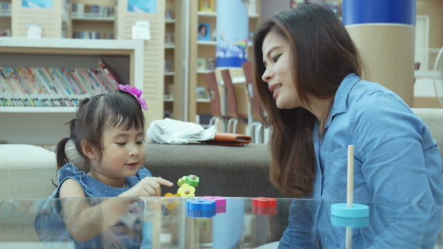 Asian baby playing toy with mother