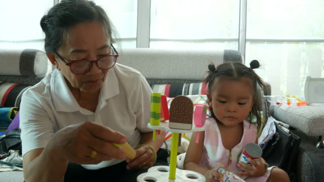 asian baby playing trade ice cream with grandmother - representing stock videos & royalty-free footage