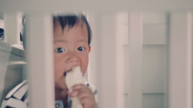 Asian baby playing with toys in crib at home
