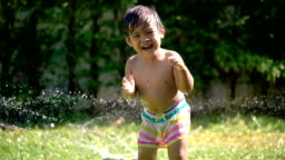 SLO MO asian baby plays water smiling and looking to camera.