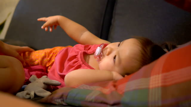 asian baby want to sleep with milk one sofa. - baby girls stock videos & royalty-free footage