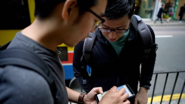 vídeos y material grabado en eventos de stock de asiático para mochileros pidiendo a local dirección al usar teléfono - preguntar