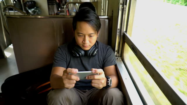 vídeos de stock e filmes b-roll de asian backpacker man gaming with his phone while traveling by local train - transporte público