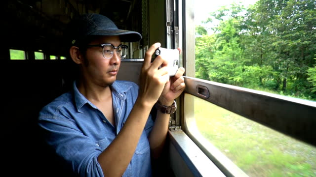 Asian Backpacker Man taking photo with DSLR on the train