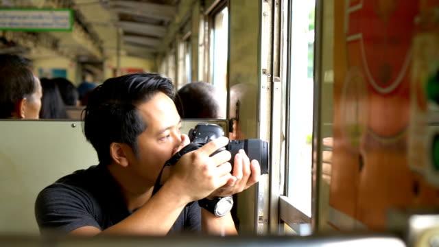 アジアのバックパッカー男電車の中でのデジタル一眼レフ撮影 - デジタル一眼レフカメラ点の映像素材/bロール