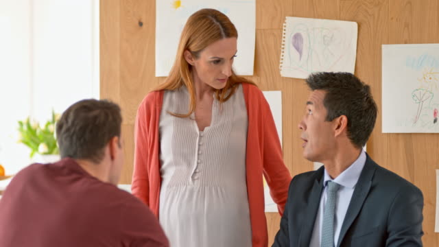 Asian banker advising a pregnant woman and her husband at their home
