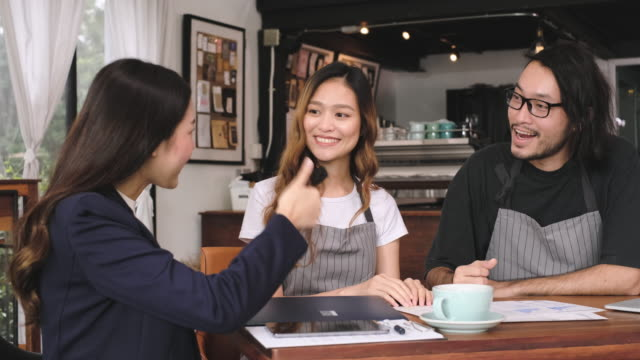 asian barista business owner show business plan to financial advisor about loan contract for open new restaurant business.small business entrepreneur - business plan stock videos & royalty-free footage