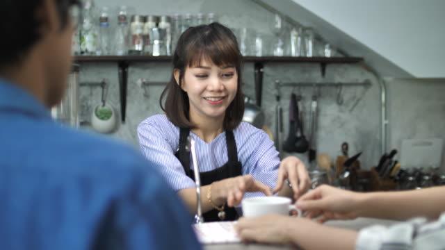 Asiatische Barista Kaffee serviert, an Kunden