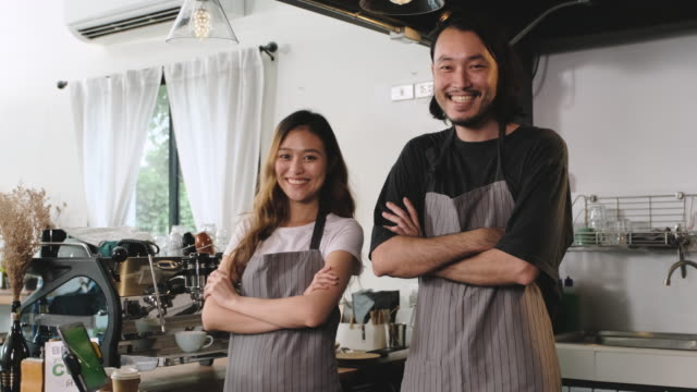 asian barista small business owner partner smiling and looking at camera at counter bar in coffee shop.start up young adult business.slow motion - employee stock videos & royalty-free footage