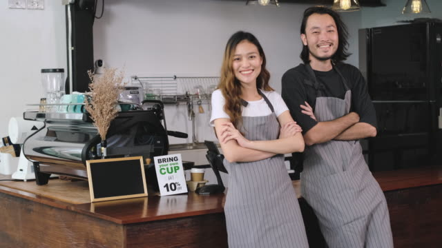 アジアのバリスタ中小企業オーナーパートナーは、コーヒーショップのカウンターバーでカメラを見て微笑んでいます。 - 外食産業関係の職業点の映像素材/bロール