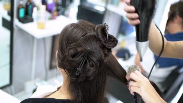 asiatische kosmetikerinnen färben haare und machen haare für customers.in schönheitssalon - schönheitssalon stock-videos und b-roll-filmmaterial