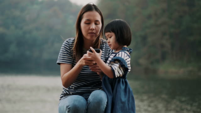 asian beautiful baby girl and her mother are using smartphone while playing and talking with friend with her positive expression on vacation time beside the river and greenery space - net sports equipment stock videos & royalty-free footage
