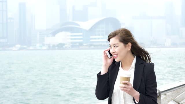 アジアの美しい電話で話しているビジネスウーマンの屋外 - ビジネスウーマン点の映像素材/bロール