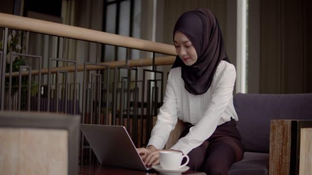コーヒーショップでフリーランスやセルフビジネスで働くアジアの美しいイスラム教徒の女性はヒジャーブを着用し、ラップトップを使用しました。 - モデスト・ファッション点の映像素材/bロール