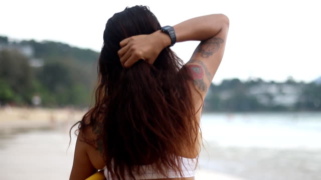 Asian beautiful surfer girl looks to the horizon