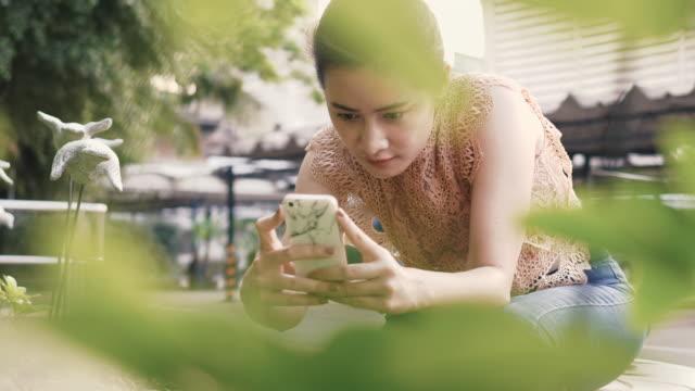 schöne asiatin nimmt ein bild im garten - zuschnappen stock-videos und b-roll-filmmaterial
