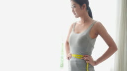 Asian beautiful woman measurement waistline with happy emotion. Concept of weight loss, diet plans, beauty, health benefits and estimate around waist.