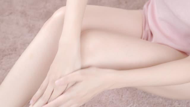 vídeos de stock, filmes e b-roll de mulher bonita asiática que senta-se em um sofá e que aplica o creme do hidratante em seu pé, tiro do close-up. conceito do cuidado do corpo, anti-cellulite, vista lateral - anti higiênico