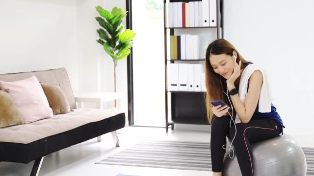 ヨガや自宅でのエクササイズの後、ヘッドフォンやスマートフォンで音楽を聴くアジアの美しい女性。体重を減らし、柔軟性を高め、形状を引き締めるための運動。 - 聞く点の映像素材/bロール