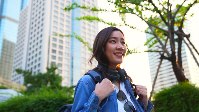 vídeos de stock e filmes b-roll de asian beautiful women wearing tourist clothes wear headphones, walk and smile in the big city in the morning. it represents the happiness of having to go on a journey again. - jaqueta jeans