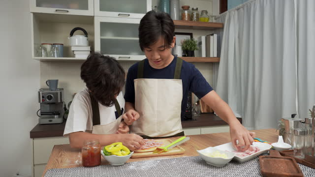 asian big brother and little brother having a fun activity to making pizza, adding ham together at weekend for dinner concept of asian family with two children, son sibling cooking food. children concentrate to do, having positive emotions. - 14 15 years stock videos & royalty-free footage