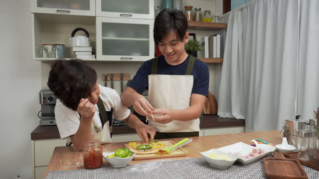 asian big brother and little brother having a fun activity to making pizza, adding sweet pepper on top of ham at weekend for dinner concept of asian family with two children, son sibling cooking food. children concentrate to do, having positive emotions. - 14 15 years stock videos & royalty-free footage