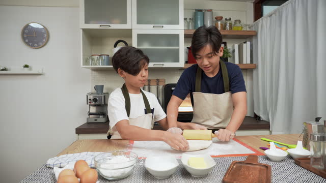 asian big brother and little brother having a fun activity to scramble thresh dough with rolling pin at the weekend. concept of asian family with two children, son sibling cooking, baking bakery.  children concentrate to do, having a positive emotion. - 14 15 years stock videos & royalty-free footage