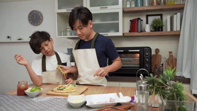 asian big brother, little brother having a fun activity to making pizza, adding sauce on top of ham, sweet pepper, cheese for dinner. concept of asian family with two children, son sibling cooking food. children concentrate, having positive emotions. - 14 15 years stock videos & royalty-free footage