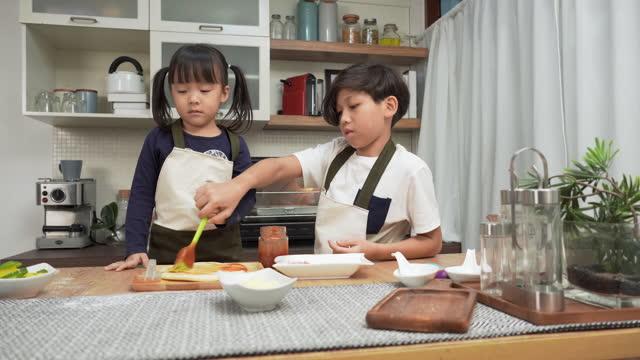 vidéos et rushes de grand frère asiatique enseignant petite sœur ayant une activité amusante à faire de la pizza, en ajoutant de la sauce, le week-end pour le dîner concept de famille asiatique avec deux enfants, fils frère et sœur cuisiner des aliments. les enfants se - son