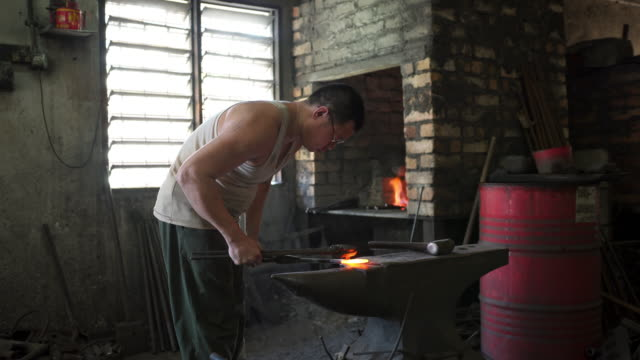 Asian blacksmith forging hot iron on anvil in his workshop