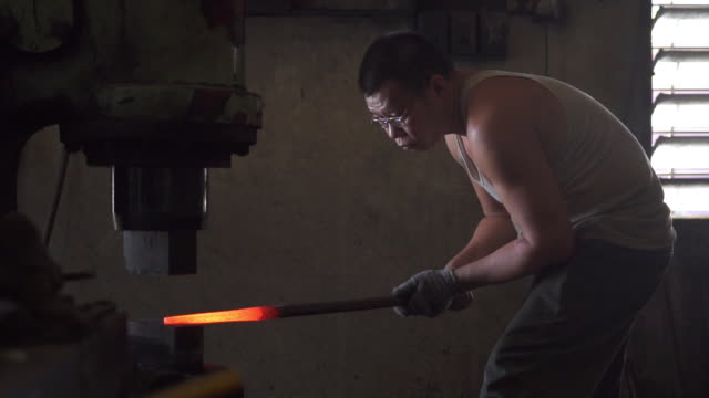 asian blacksmith working with iron his workshop - moulding a shape stock videos & royalty-free footage