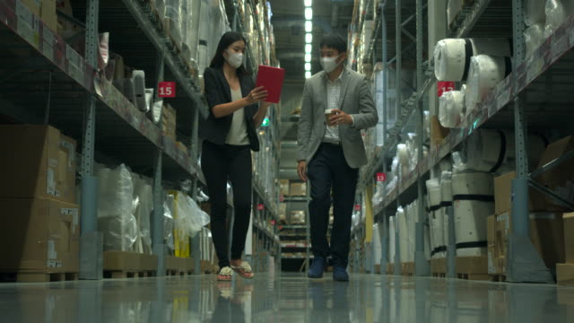 asian boss and secretary walking in the aisle of the warehouse and check the product using the internet via tablet. - compartment stock videos & royalty-free footage
