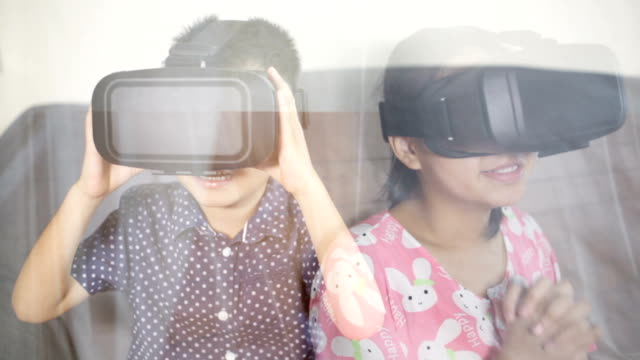 Asian boy and girl playing VR indoors