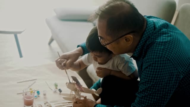 asian boy and grandfather painting a toy model airplane (slow motion) - art and craft stock videos & royalty-free footage