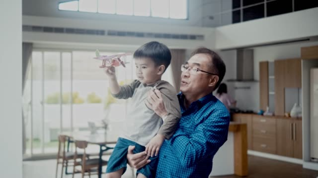 asian boy and his grandfather flying a model airplane (slow motion) - grandchild stock videos & royalty-free footage