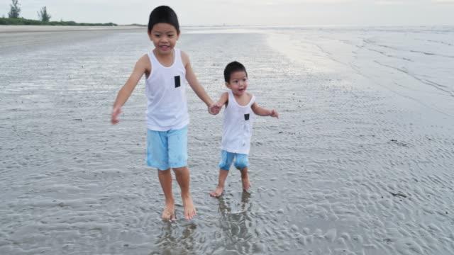 アジアの男の子の兄弟は、ビーチで楽しんで、一緒に遊んでいます。 - 兄弟点の映像素材/bロール