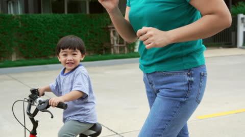 asiatische junge fahrrad mit mutter - teaching stock-videos und b-roll-filmmaterial