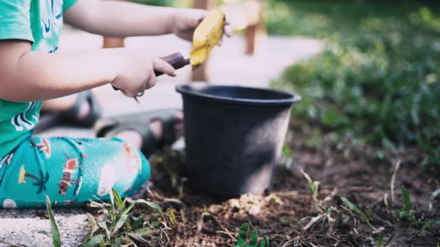 アジアの少年は庭の土壌を掘る - 作物点の映像素材/bロール