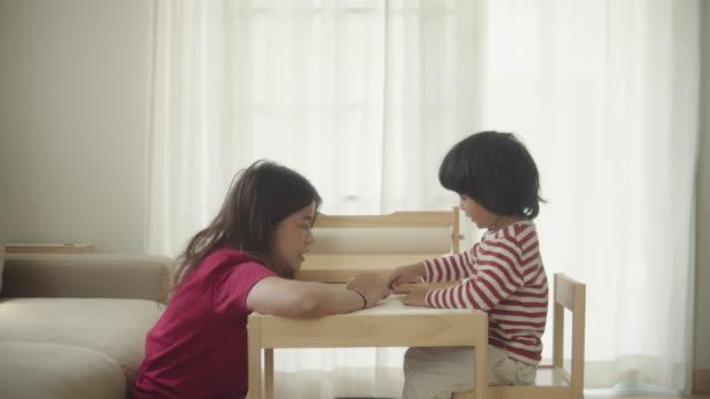vídeos de stock, filmes e b-roll de menino asiático fazendo lição de casa com a mãe na parte da manhã - etnia oriental