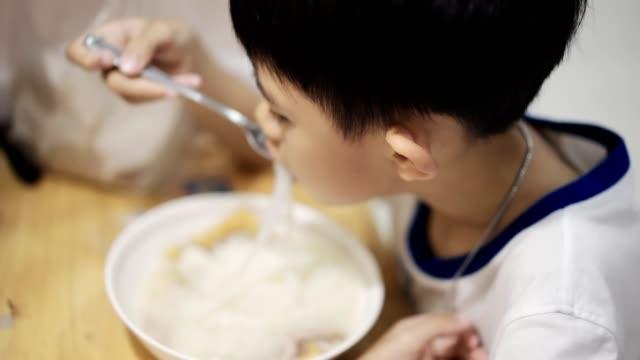 vidéos et rushes de nouilles asiatiques de garçon mangeant - bol à soupe