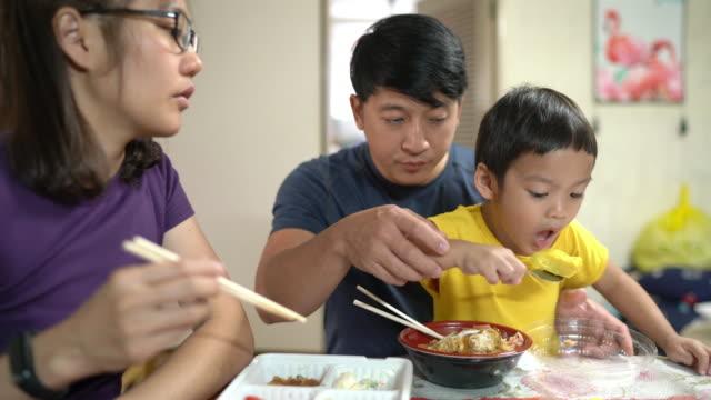 たまご焼き、お父さんとお母さんと一緒に日本の卵を食べるアジアの男の子 - 両親点の映像素材/bロール