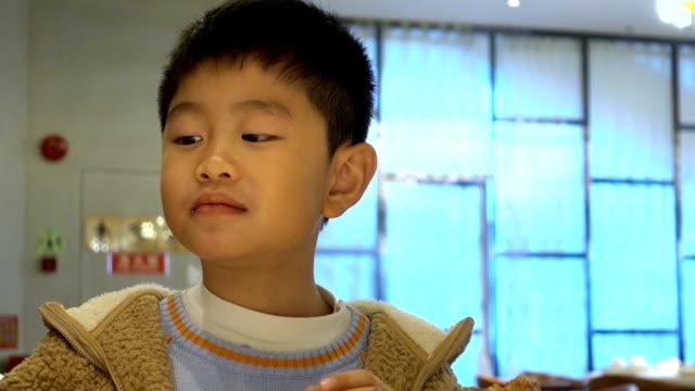 asian boy enjoying lamb skewer and licking lips in restaurant - skewer stock videos & royalty-free footage