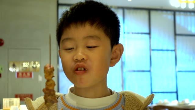 asian boy enjoying lamb skewer in restaurant - skewer stock videos & royalty-free footage