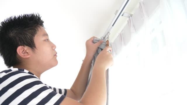 家の窓でカーテンを羽ばたかすアジアの少年、家のコンセプトを動かす。 - カーテン止め点の映像素材/bロール