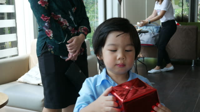 Asian boy having fun open gift